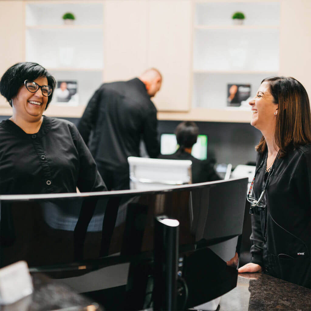 The two team members laughing together in our office